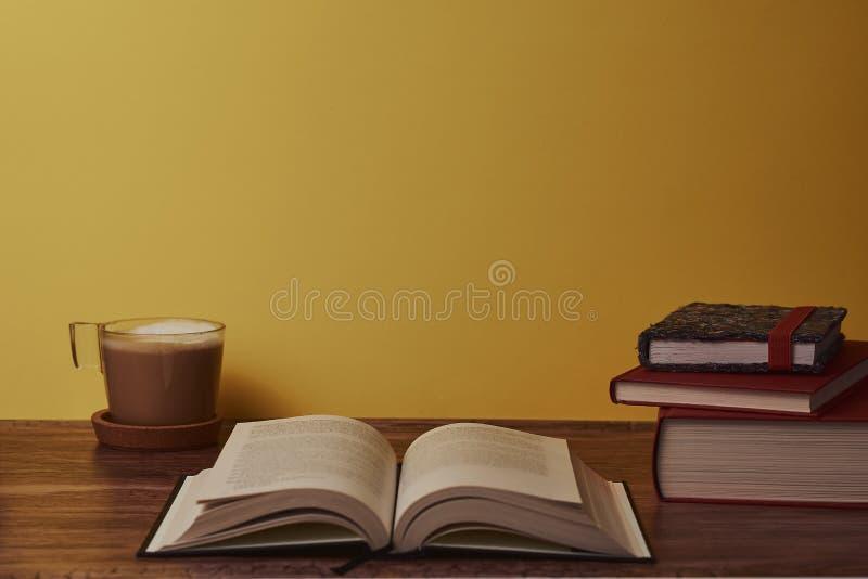Koffie met melk en boeken op een bruine houten lijst stock foto