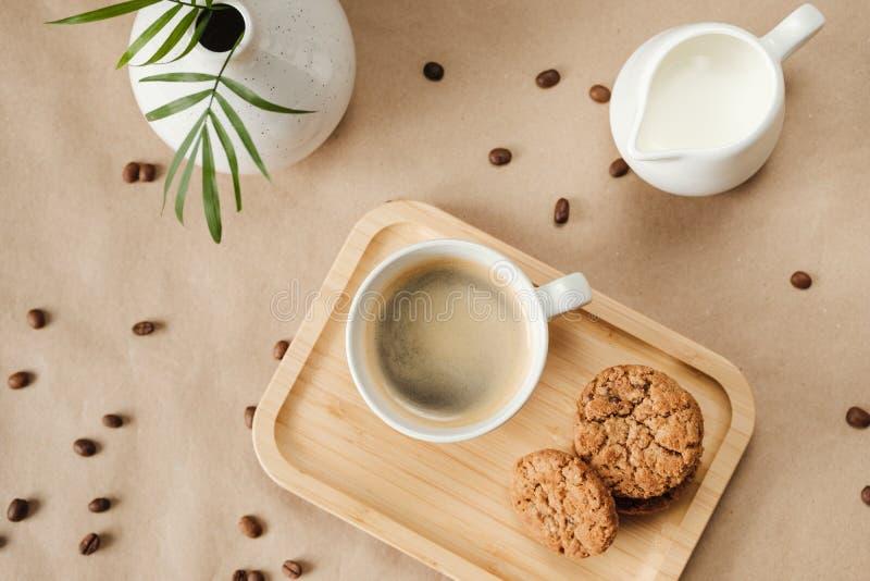 Koffie met melk en havermeelkoekjes op een houten dienblad stock foto