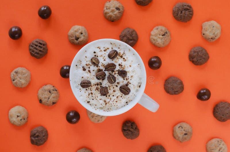 Koffie met melk en koffiebonen op oranje achtergrond met koekjes Vlak leg stock afbeelding