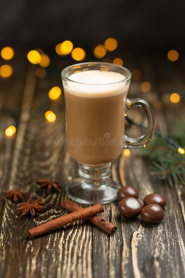 Koffie met melk, latte met pijpjes kaneel en anijsplantsterren en snoepjes, Kerstboom op een houten achtergrond, met lichten van  stock fotografie