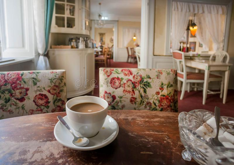 Koffie met melk op retro lijst binnen oud restaurant, met uitstekend meubilair en comfortabele ruimten van historisch huis royalty-vrije stock afbeeldingen