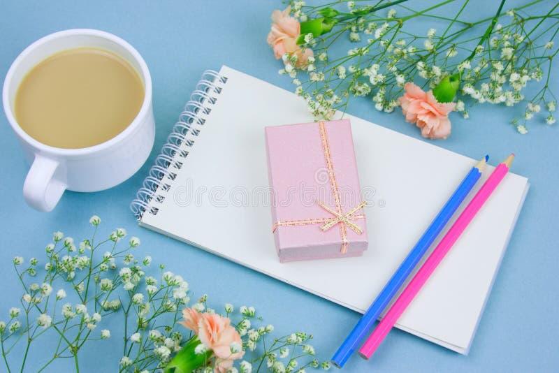 koffie met roomkop, notitieboekje, potloden en roze giftdoos met bloemenkader op een blauwe achtergrond stock foto