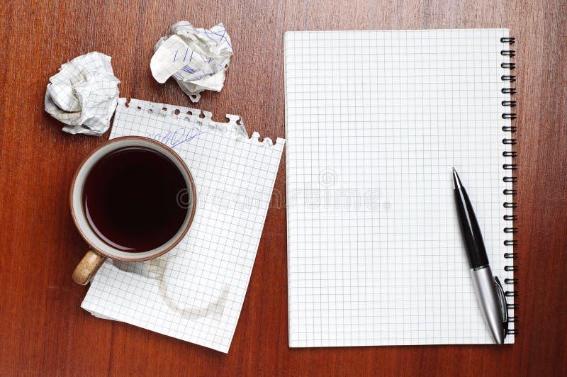 Koffie, notitieboekje, pen en verfrommeld document stock afbeelding