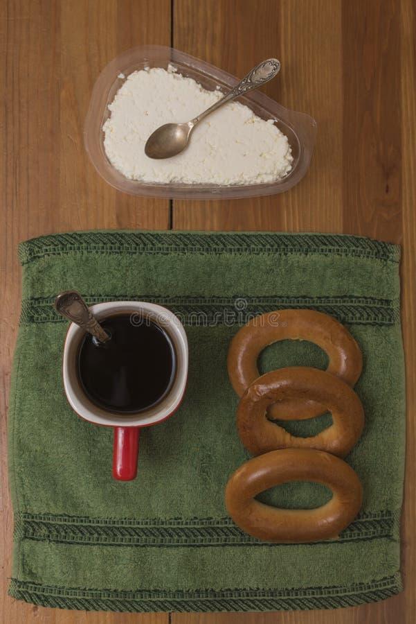 Koffie, ongezuurde broodjes en melkkwark op een groen servet stock afbeelding