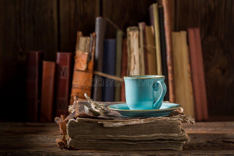Koffie op boek in blauw porselein in bibliotheek stock fotografie
