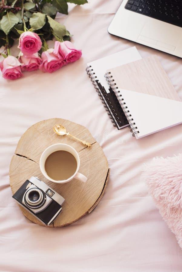 Koffie, oude uitstekende camera in bed op roze bladen Rozen, notitieboekjes en laptop rond Freelance de vrouwelijkheidswerkruimte stock foto
