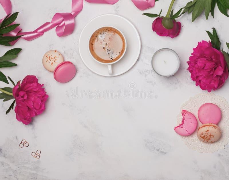 Koffie, roze pioenen en macarons op de marmeren lijst royalty-vrije stock foto's
