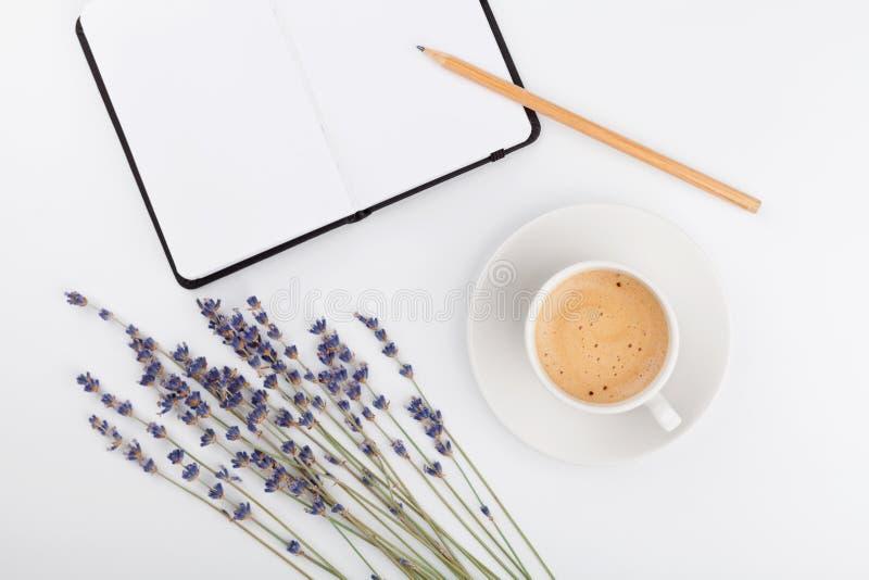 Koffie, schone notitieboekje en lavendelbloem op de witte mening van de lijstbovenkant Vrouwen werkend bureau Comfortabel ontbijt stock foto's