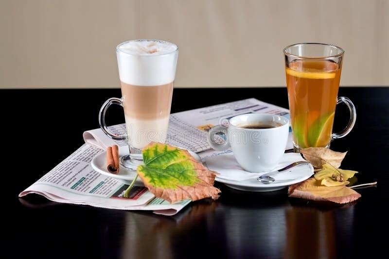 Koffie, thee, latte met droge bladeren en kranten stock afbeeldingen