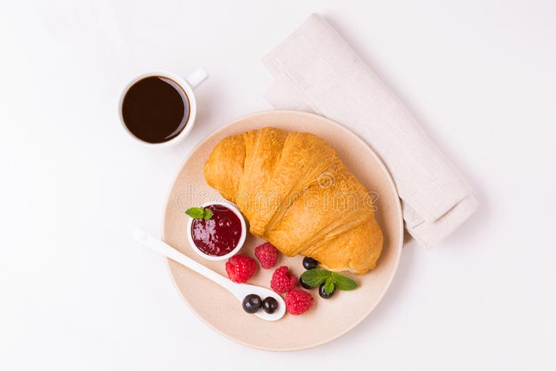 Koffie, vers croissant met jam en bessen voor ontbijt stock foto's