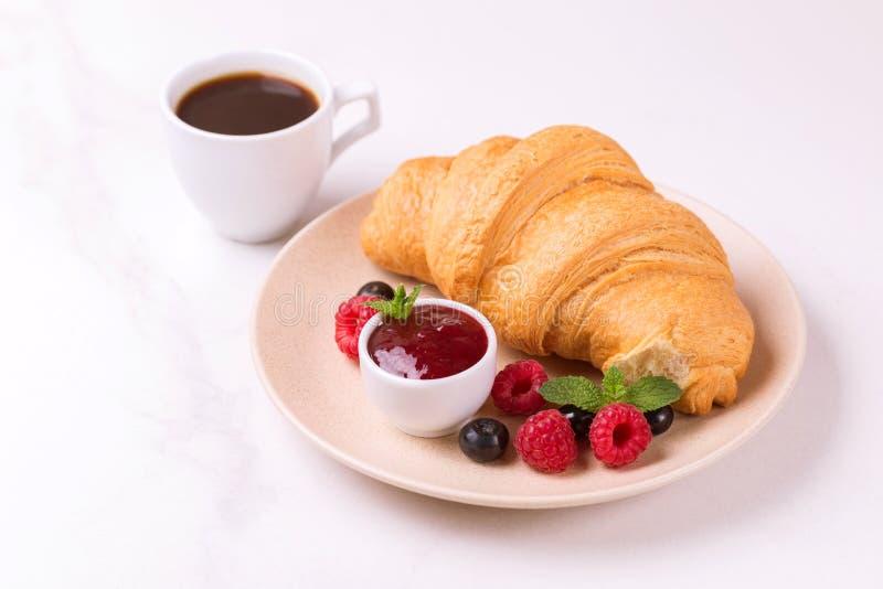Koffie, vers croissant met jam en bessen voor ontbijt royalty-vrije stock afbeelding