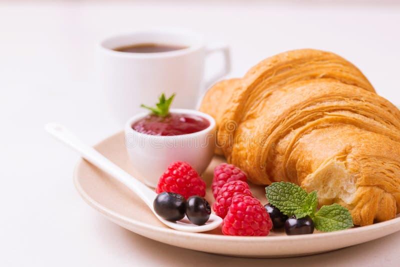 Koffie, vers croissant met jam en bessen voor ontbijt royalty-vrije stock afbeeldingen