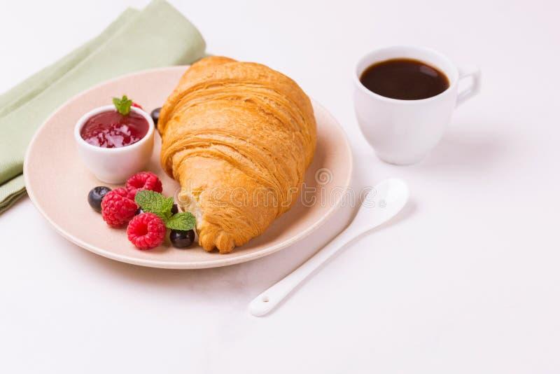 Koffie, vers croissant met jam en bessen voor ontbijt stock afbeeldingen