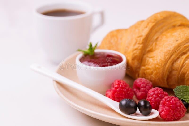 Koffie, vers croissant met jam en bessen voor ontbijt stock fotografie