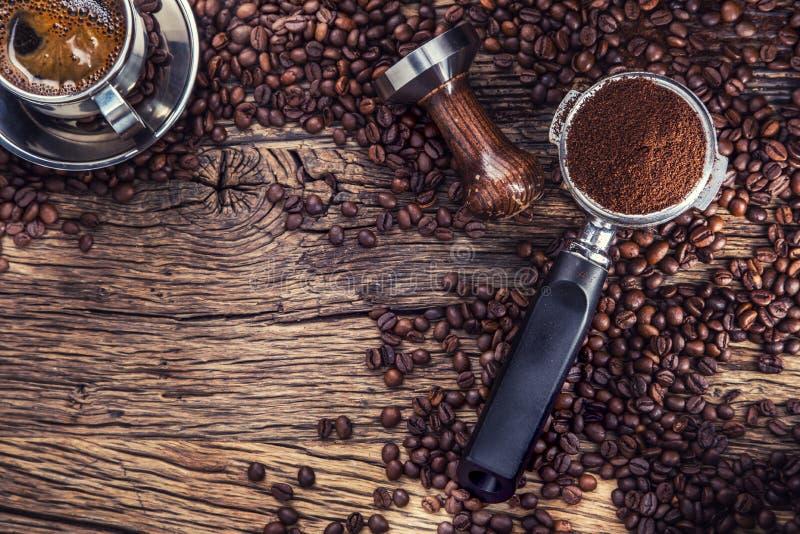 Koffie Zwarte koffie met koffiebonen en portafilter op oude eiken houten lijst stock afbeeldingen