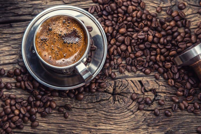 Koffie Zwarte koffie met koffiebonen en portafilter op oude eiken houten lijst stock afbeelding