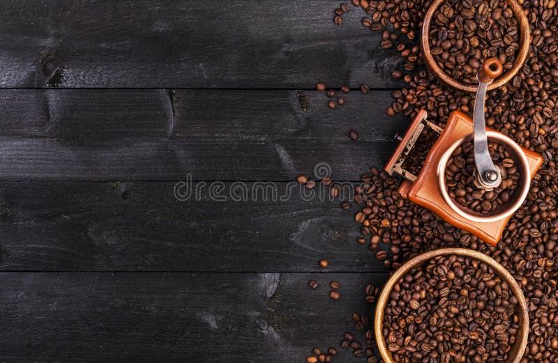 Koffieachtergrond, hoogste mening met exemplaarruimte Grondkoffie, molen, kom van geroosterde koffiebonen op donkere houten achte stock foto