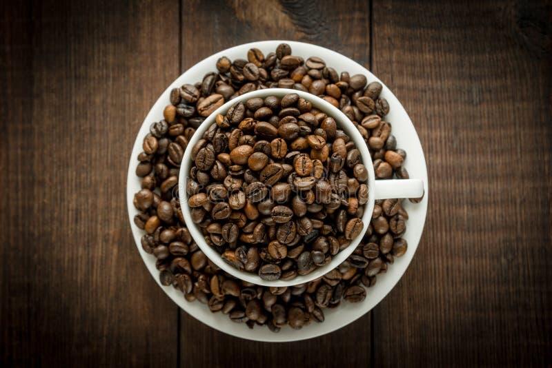 Koffiebonen in de kop op donkere houten achtergrond stock foto's