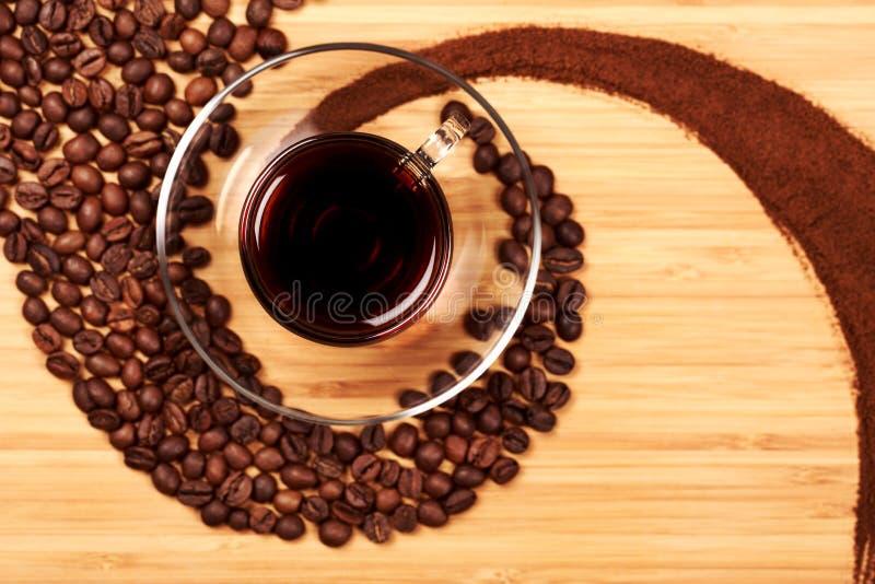 Koffiebonen in de vorm van een werveling met glas royalty-vrije stock foto