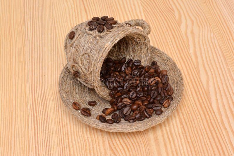 Koffiebonen in een decoratieve kop en een schotel op de houten oppervlakte stock afbeelding