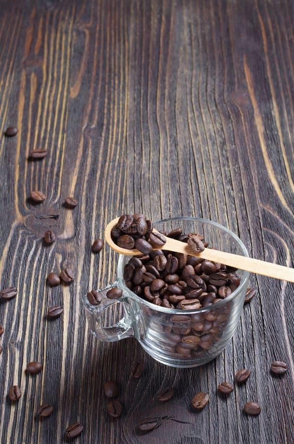 Koffiebonen in een glaskop met een houten lepel royalty-vrije stock foto