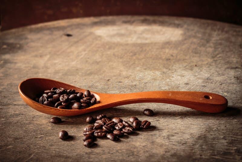Koffiebonen in een houten lepel en op oude houten royalty-vrije stock afbeelding