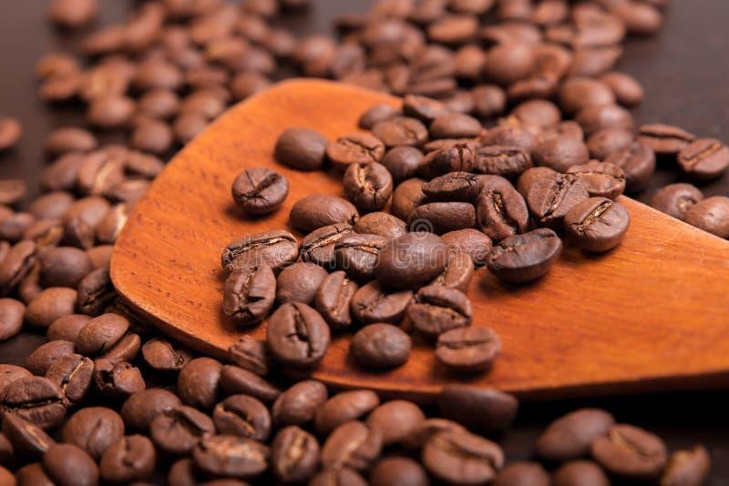 Koffiebonen in een houten lepel op bruine lijst royalty-vrije stock afbeelding