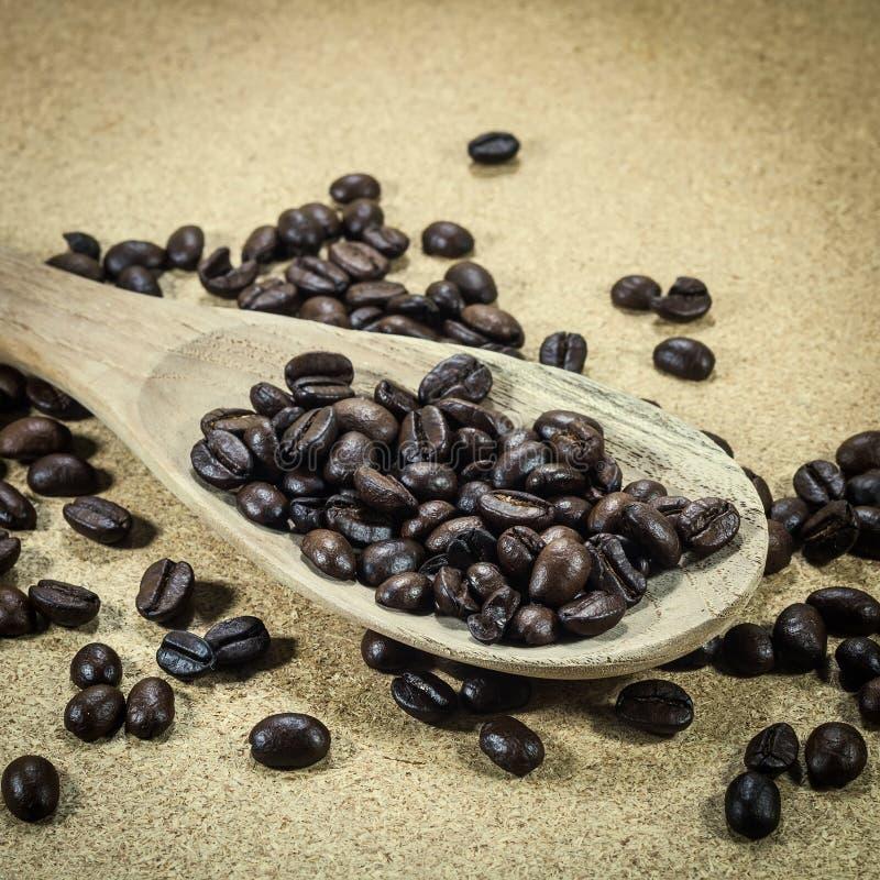 Koffiebonen in een oude houten lepel royalty-vrije stock foto's