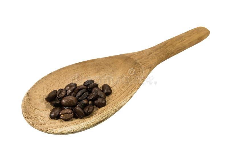 Koffiebonen in een oude houten lepel op de witte achtergrond stock foto's