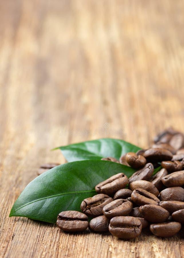 Koffiebonen en blad dichte omhooggaand op houten lijst stock fotografie