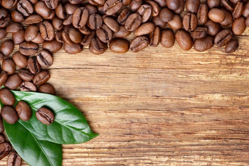Koffiebonen en blad op houten achtergrond stock afbeeldingen