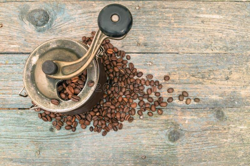 Koffiebonen en molens op oude houten lijst stock afbeelding