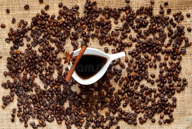 Koffiebonen en uitstekende witte ceramische kop van koffie, pijpjes kaneel, anijsplantsterren op jutezak De ruimte van het exempl royalty-vrije stock foto's