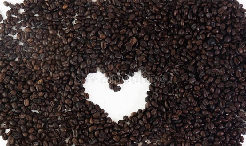 Koffiebonen in hartvorm op witte geïsoleerde achtergrond royalty-vrije stock foto