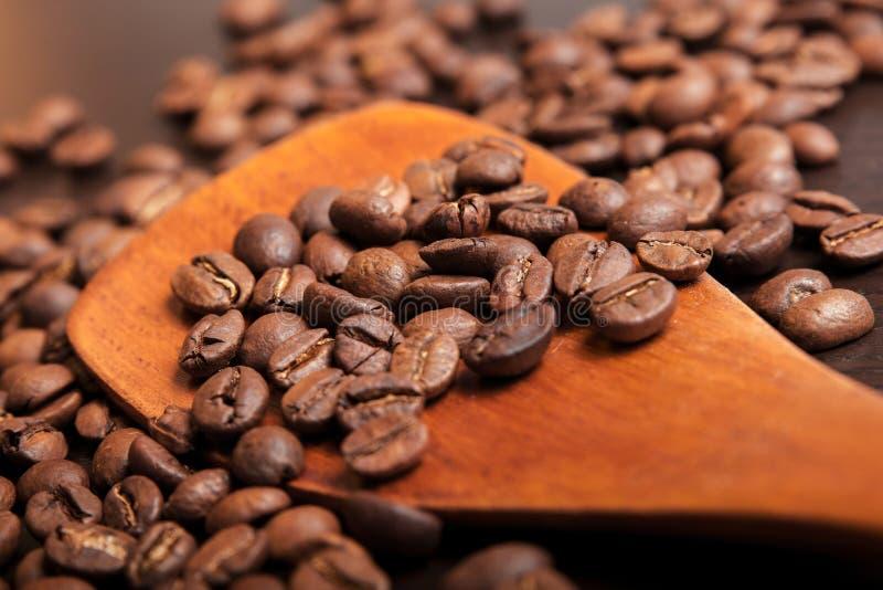Koffiebonen in houten lepel op bruine lijst royalty-vrije stock afbeelding