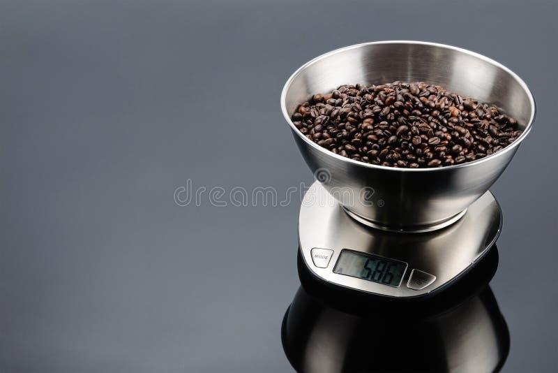Koffiebonen in kom op elektronische schaal op grijze spiegelachtergrond met exemplaarruimte stock afbeeldingen