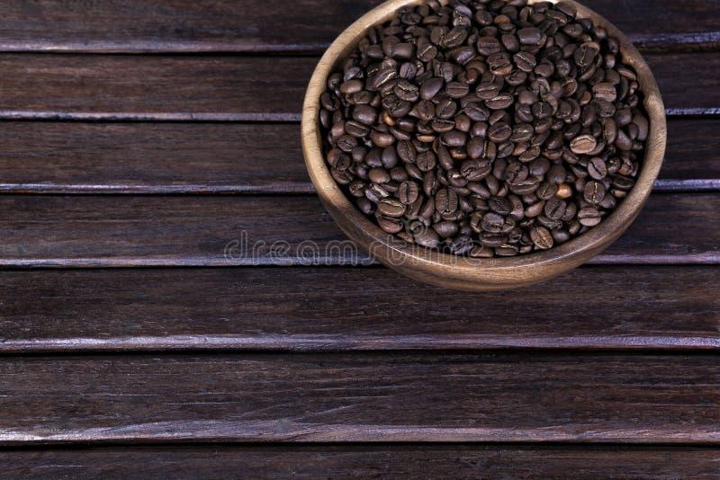 Koffiebonen op een donkere houten achtergrond grunge, koffie in de houten plaat op houten royalty-vrije stock foto