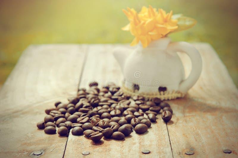 Koffiebonen op grunge houten achtergrond met Ixora-bloempot en stock foto