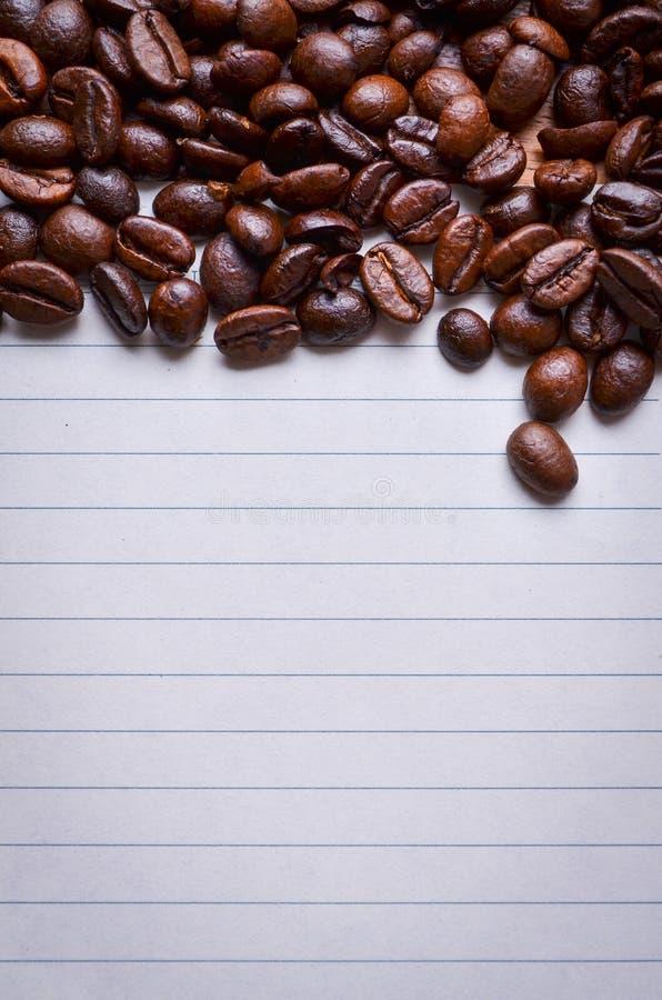 Koffiebonen op papier voor nota's stock fotografie