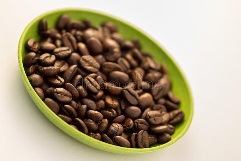 Koffiebonen in Overgehelde Schotel stock foto's