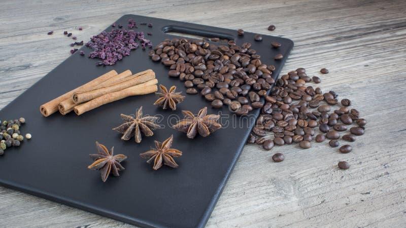 Koffiebonen, pijpjes kaneel en steranijsplant Kruiden en voedsel op de houten lijst Ingrediënten voor het maken van koffie royalty-vrije stock fotografie