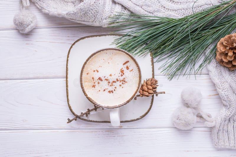 Koffiecappuccino met kaneel, een tak van een pijnboomboom en gebreide toebehoren op een houten achtergrond Vrije ruimte stock foto