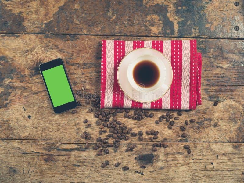 Koffieconcept met kop en een slimme telefoon stock afbeelding