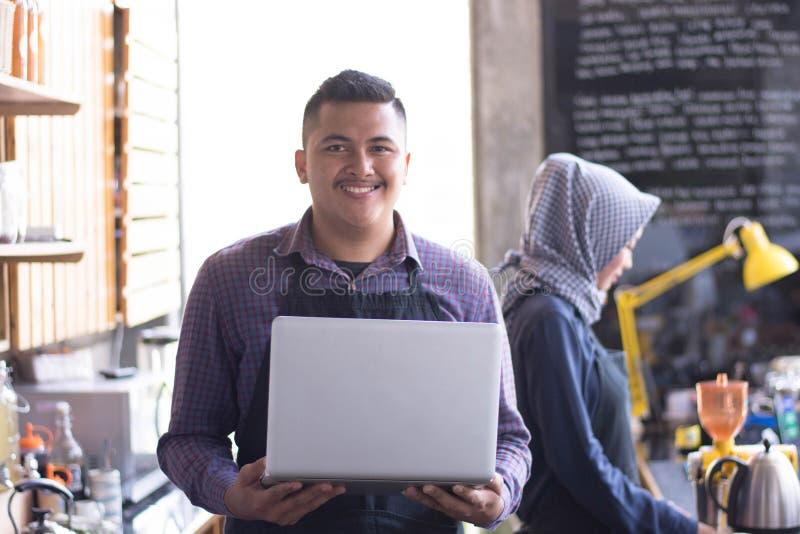 Koffieeigenaar bij zijn koffiewinkel die tabletcomputer met behulp van zijn partnerzitting op een achtergrond royalty-vrije stock foto's