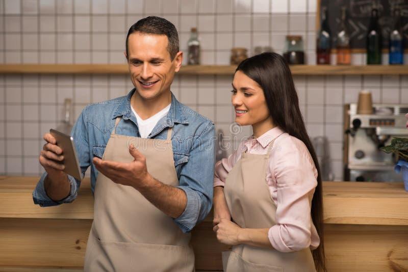 Koffieeigenaar die iets tonen aan serveerster op digitale tablet stock afbeeldingen
