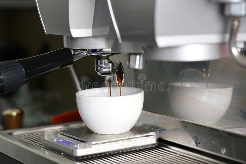 Koffieextractie het gieten in een kop van professionele koffiemachine met bar binnenlandse achtergrond stock afbeelding