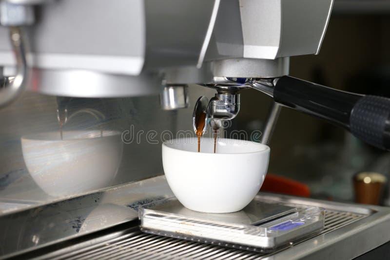 Koffieextractie het gieten in een kop van professionele koffiemachine met bar binnenlandse achtergrond stock afbeeldingen