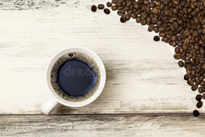 Koffiekop en bonen op een houten lijst royalty-vrije stock afbeelding