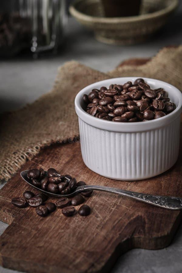 Koffiekop en bonen op oude keukenlijst stock foto