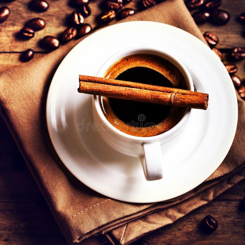 Koffiekop en geroosterde koffiebonen op houten bruine achtergrond stock fotografie